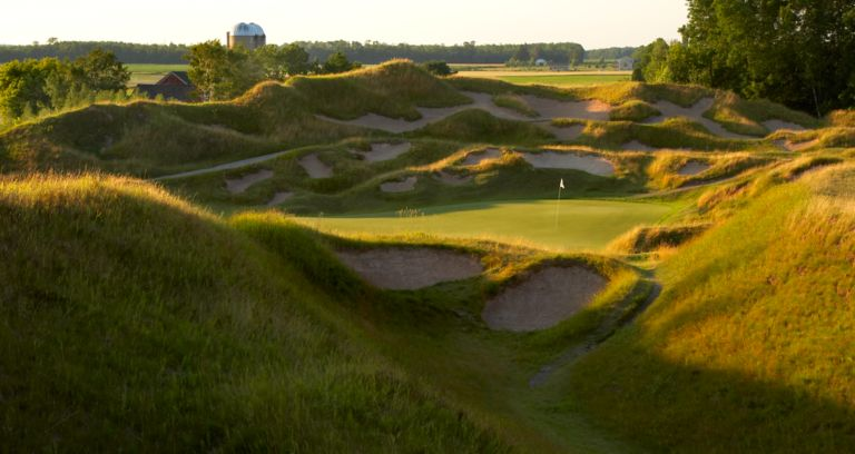 The green of the 13th hole on the Irish course with sand traps.