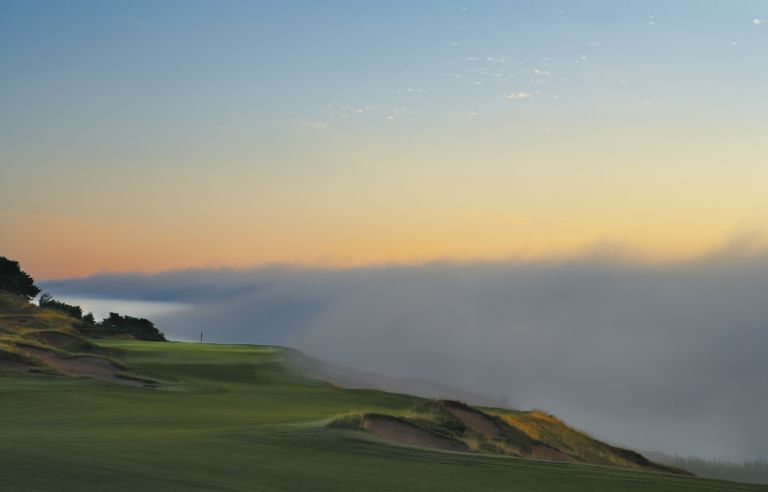 The green of the Straights Course hole 8 in the distance with Lake Michigan fog rolling in on the right side.