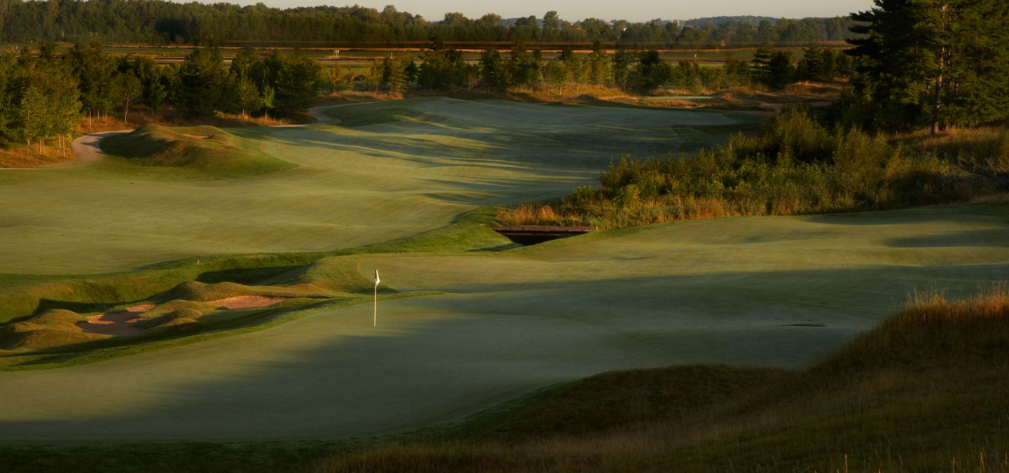 A side view of the green and flag stick with mounds and sand traps of hole 14 on the Irish Course.