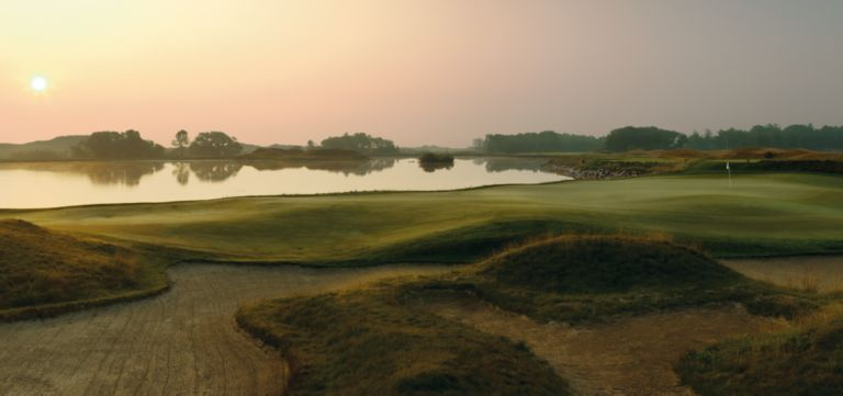 The green and fairway of hole 17 on the irish Course  with water on the left side of the fairway.