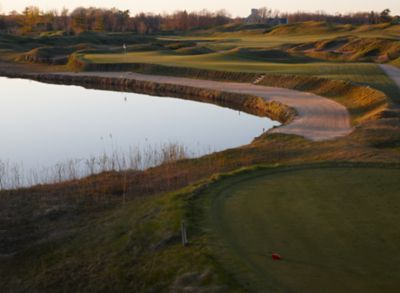 A view of the green of the third hole of the Irish Course at Whistling Stratis with a sand bunker on the left.