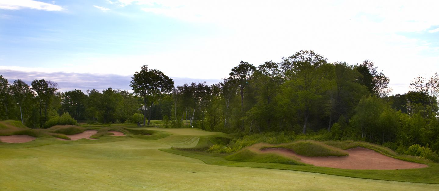 A view of the green of hole 7 of the Irish Course from the fairway with sand bunkers on the right side.