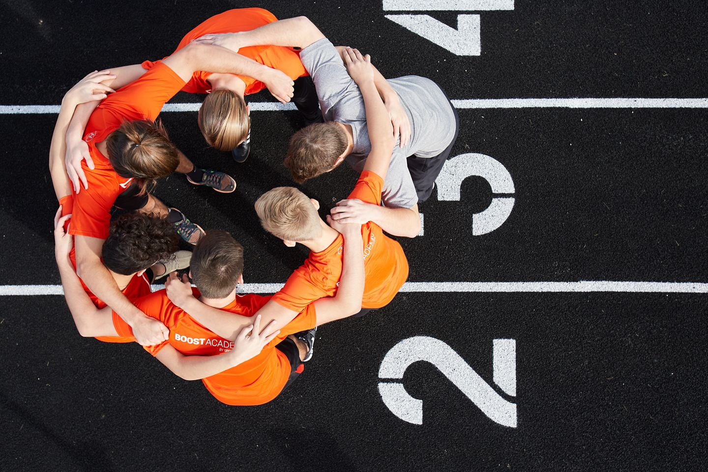 youth in a huddle on a sports track