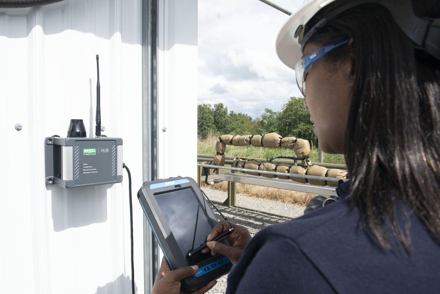 A woman monitors an oil & gas worksite from the ALTAIR io360 hub and tablet device