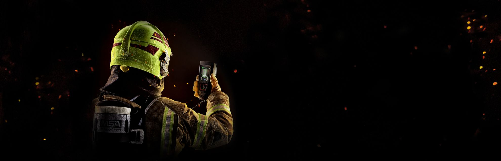 A firefighter holding Lunar, looking at the screen.