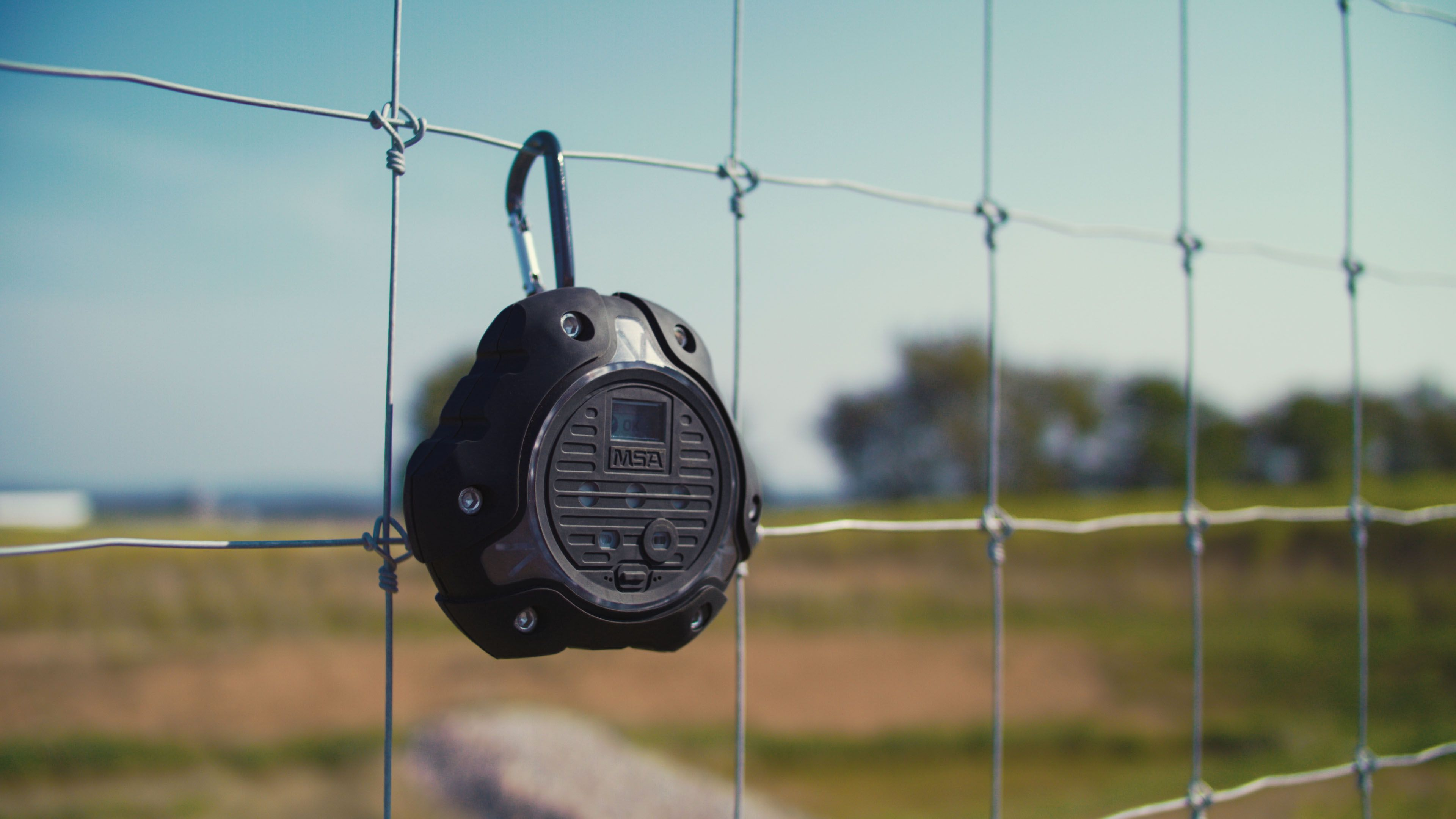The ALTAIR io360 gas detector hanging from a fence